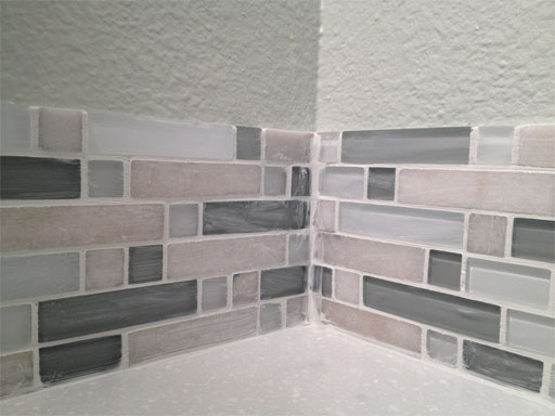 DIY kitchen backsplash: grouting the corner where the tiles meet.