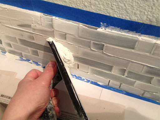 DIY kitchen backsplash: spreading wet grout over tiles.