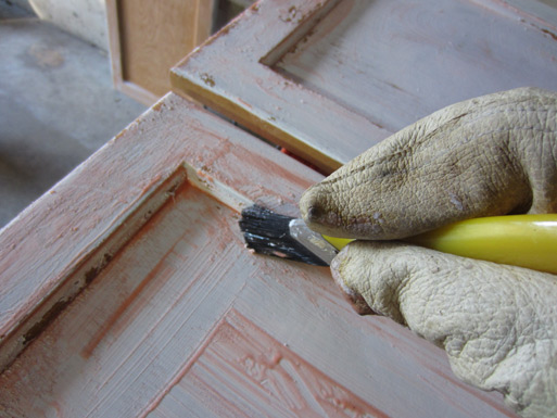 preparing kitchen cabinets for painting with stripping gel and a brush