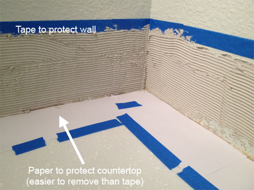 DIY kitchen backsplash: masking off the work area with painter's tape and printer paper.