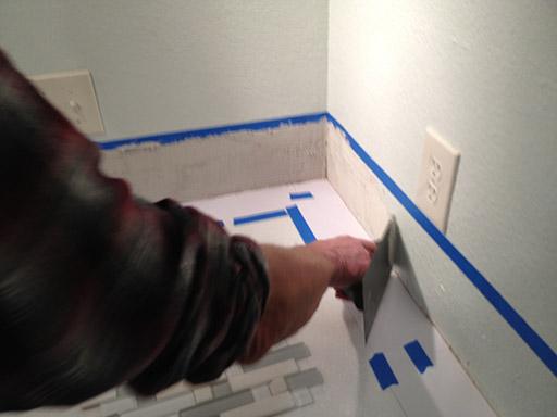 installing backsplash tiles spreading mortar on wall v notch trowel