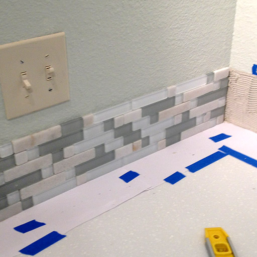 DIY kitchen backsplash in progress. Figuring out how to meet the tiles in the corner was a brief challenge, and we decided not to overlap them.