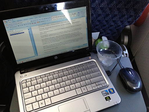 5 best tech travel accessories travel mouse and laptop on a tray table