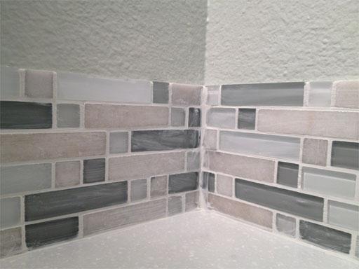 DIY kitchen backsplash: grouting the corner where the tiles meet.