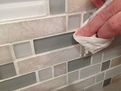 DIY kitchen backsplash: polish grout off the tile corners so they look nice and crisp.