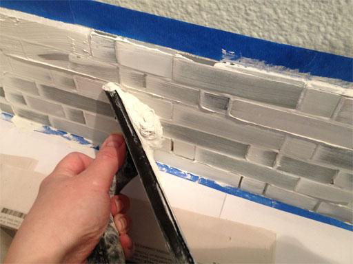 DIY kitchen backsplash: spreading wet grout over tiles.